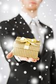 love, romance, holiday, celebration concept - man giving gift box