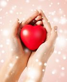 health, love and charity concept - woman hands with heart