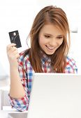 online and internet shopping concept - happy teenage girl with laptop and credit card