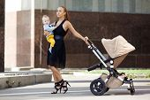 Fashionable modern mother on a city street with a pram. Young mother walks with a  child in the city
