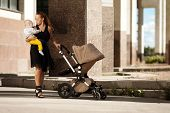 Trendy modern mother on a city street with a pram. Young mother walks with a child in  the city. Bea