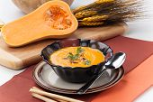 stock photo of butternut  - Hot delicious pumpkin soup in a bowl - JPG