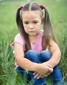 Sad little girl is sitting on green grass, outdoor shoot