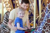 stock photo of merry-go-round  - happy family of two at merry - JPG