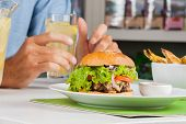 Closeup of stuffed burger with man's hand holding drink at table