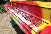 picture of rainbow piano  - Colorfully decorated old piano stands outside in a park - JPG