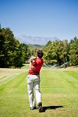 Golf player performs a tee shot using a driver club. One young caucasian male golfer, red shirt and