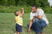 Happy African American Father and Son Playing Outdoor Park in Summer