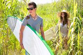 Surfer boy and girl walking in the green jungle with sunglasses