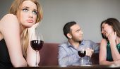 stock photo of beside  - Blonde woman feeling jealous of couple flirting beside her in a bar - JPG