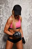 Sporty woman with dumbbell on grey concrete background