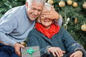 Happy senior man surprising woman with Christmas gift in store