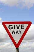 Closeup of give way road sign against cloudy sky