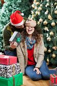 Young man in Santa hat surprising woman with Christmas gifts in store