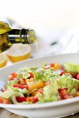 Olive oil is being added into a vegetable salad