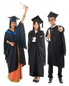 Full body group of multi races university student in graduation gown standing isolated on white back