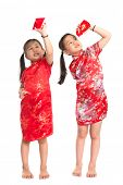 Happy Asian girls peeking into red packet during Chinese New Year, with traditional Cheongsam full l