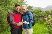 Happy couple on a hike looking at photo on smartphone in the countryside