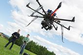 Young male engineers operating UAV helicopter against cloudy sky