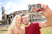 Tourist couple on travel taking pictures by Coliseum in Rome. Happy young romantic couple traveling in Italy, Europe taking self-portrait with smartphone camera in front of Colosseum. Man and woman.