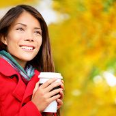 Coffee woman drinking coffee outside in fall forest. Beautiful young woman drinking hot drink from d