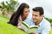 Beautiful couple on a romantic date outdoors reading a book