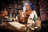 Vintage alchemist adding herbs to a smoking kettle