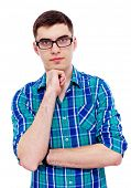 Closeup portrait of serious young man in glasses with hand on his chin. Isolated on white background