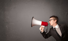 stock photo of shout  - Guy shouting into megaphone on copy space background - JPG
