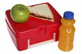 Back to School still life with apple, sandwich, juice, and red lunchbox on white