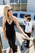 Full length of rich woman boarding private jet with pilot and airhostess standing by at airport term
