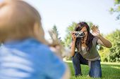 Happy young mother photographing son through camera in park