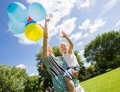 Smiling mother and daughter with helium balloons in park