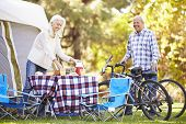 Senior Couple Riding Bikes On Camping Holiday In Countryside