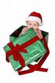 Baby wearing santa hat inside green and red Christmas present box on white