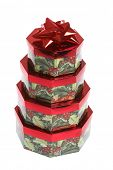 Octagonal Christmas presents stacked with red bow on white background