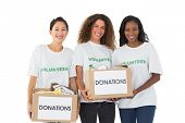 Team of volunteers smiling at camera holding donations boxes on white background