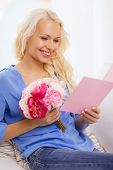 holiday, celebration, home and birthday concept - smiling young woman with greeting card and bouquet of flowers