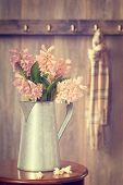Country house hallway with jug filled with spring hyacinths - vintage tone effect added