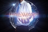 Businessman presenting the word malware against glowing sphere on black background