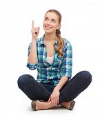 happiness, advertising and people concept - smiling young woman pointing finger up