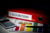 The word algorithms on red business binder on a desk