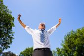 Low angle view of successful businessman with arms outstretched standing against blue sky