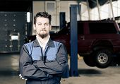Confident car mechanic in car service