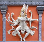 stock photo of vinayagar  - Nataraj Dancing Form of Lord Shiva Hindu God Orange and White Statue on Temple Exterior Wall Relief - JPG