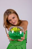 Pretty Woman Holding Gift With Flower In Glass Bowl