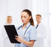 healthcare and medicine concept - serious female doctor or nurse with stethoscope and clipboard