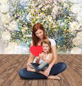 childhood, parenting and relationship concept - happy mother with adorable little girl and red heart