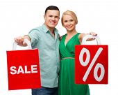 happiness, shopping and couple concept - smiling couple with shopping bags with sale and percent sig