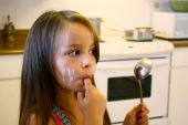Young Girl Licking Spoon